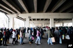 Furloughed federal workers and their families who are affected by the partial government shutdown wait in line to receive food distributed by Philabundance volunteers under Interstate 95 in Philadelphia, Jan. 23, 2019.
