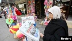 Seorang perempuan Palestina membaca koran di Khan Younis, bagian selatan Jalur Gaza (18/3). (Reuters/Ibraheem Abu Mustafa)
