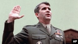 FILE - Lt. Col. Oliver North is sworn in on Capitol Hill in Washington prior to testifying before the House Foreign Affairs Committee on the Iran-Contra scandal, Dec. 18, 1986.