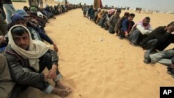Bangladeshi evacuees wait for food at a refugee camp near the Libyan and Tunisian border crossing of Ras Jdir after fleeing unrest in Libya March 11, 2011