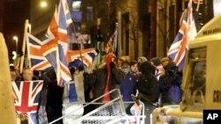 Para pendukung setia Inggris terus berbaris menuju balai kota Irlandia di tengah-tengah penjagaan polisi yang ketat di Belfast (3/1).