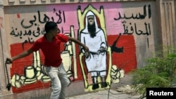 A protester throws a chain next to a graffiti on the wall depicting the newly appointed governor of Luxor Adel Mohamed al-Khayat, as a terrorist, as protests gather in front of the governorate building to protest his appointment in Luxor, June 19, 2013.