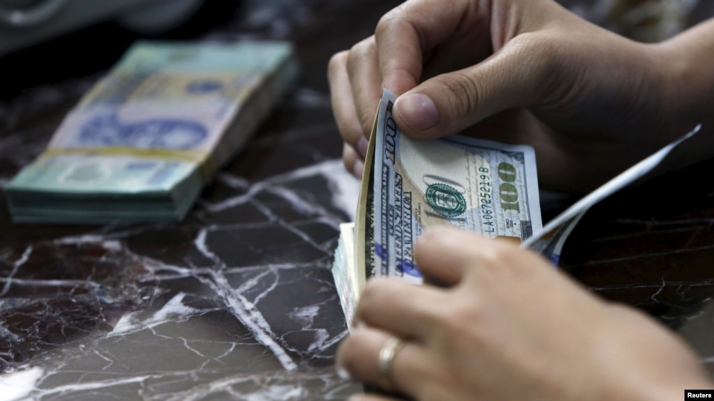 Một nhân viên ngân hàng ở Hà Nội đếm đôla.