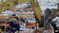 Members of Missouri Task Force One search-and-rescue team stand by as heavy equipment moves debris from a tornado-damaged Home Depot store, in Joplin , Missouri, May 24, 2011