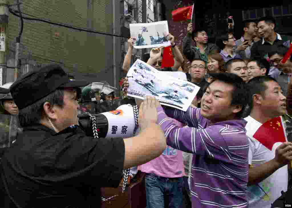 Protesters hold images they claim show Japanese imperial army soldiers who killed Chinese during World War II at an anti-Japan protest in Chengdu, Sichuan, China, Sepember 18, 2012.