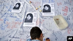 A boy signs a petition calling for an end to stoning during a demonstration by members of the International Committee Against Stoning in London, demanding the release of Sakineh Ashtiani, 24 Jul 2010