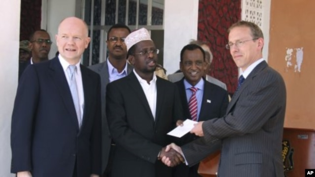 Somali President Sharif Sheik Ahmed, center, receives diplomatic credentials from British ambassador to Somalia Matt Baugh, right, and British Foreign Secretary William Hague, at Mogadishu's presidential palace, February 2, 2012.