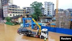 中國廣西柳州市的交通警察把街道上泡在洪水裡的汽車運走。 (2021年7月2日)