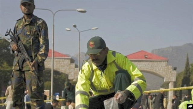 Official picks up pieces of flesh belonging to suicide attacker outside Pakistani naval headquarters in Islamabad, 2 Dec 2009