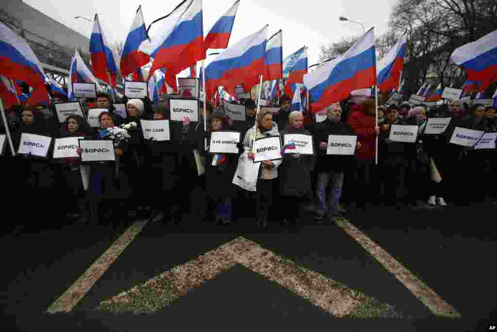 "People carry Russian national flags as they march with posters reading ""I have no fear, fight!"" near the place opposition leader Boris Nemtsov was gunned down on Friday, near the Kremlin, in Moscow, Russia, March 1, 2015."