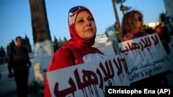 "Dua perempuan Tunisia ikut unjuk rasa dengan membawa tulisan ""Tidak untuk Terorisme"" dalam aksi di Tunis, Jumat (20/3)."