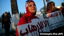 Một phụ nữ cầm tấm bảng với nội dung 'Nói không với chủ nghĩa khủng bố'
