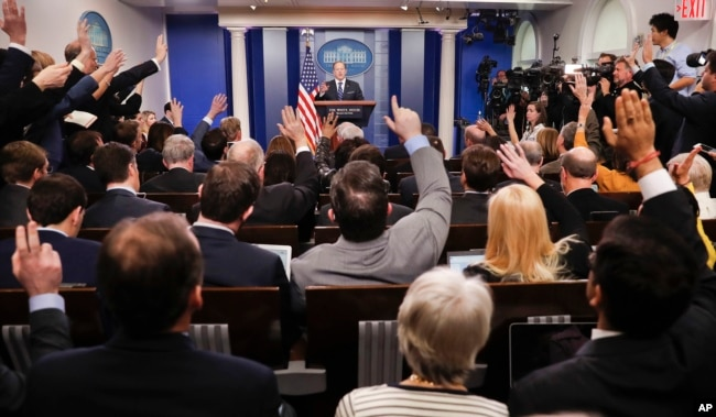 FILE - Reporters raise their hands as then-White House press secretary Sean Spicer takes questions during the daily briefing in the Brady Press Briefing Room of the White House in Washington, Feb. 22, 2017.
