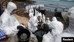 Thai soldiers and energy company workers in white biohazard suits take part in a clean-up operation at Ao Prao Beach on Koh Samet, Rayong, Thailand, July 30, 2013.