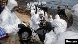 Una cadena humana conformada por soldados tailandeses y empleados de la compañía de energía PTT trabajan limpiando las playas en la isla de Samet.