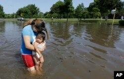 Phụ nữ bồng con qua khu vực ngập nước ở Houston, Texas, ngày 26/5/2015.