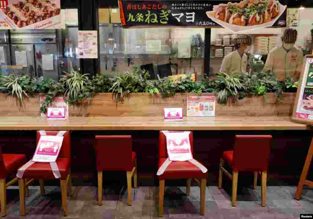 Social distancing signs are place on a table and chairs at a restaurant in Japan's supermarket group Aeon's shopping mall as the mall reopens amid the coronavirus disease (COVID-19) outbreak in Chiba, Japan May 28, 2020. REUTERS/Kim Kyung-Hoon