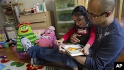 Christopher Astacio membaca dengan putrinya Cristina, 2, yang didiagnosis memiliki bentuk autisme yang lebih ringan, di rumah mereka di New York. (Foto: Dok)