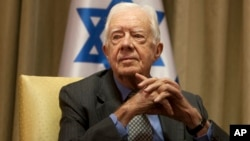 FILE - Former U.S. President Jimmy Carter sits prior to a meeting with Shimon Peres, then Israel's president, in Jerusalem, Oct. 21, 2012.
