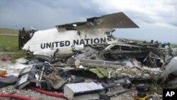 Watu wanasimama kuangalia mabaki ya ndege ya Umoja wa mataifa iliyoanguka Kinshasa ilipokuwa inatua, Aprili 4, 2011.