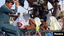 Families sit at the back of a van with their belongings, while fleeing a military offensive against the Pakistani Taliban, as they enter Bannu, located in Khyber Pakhtunkhwa province, Jan. 22, 2014.