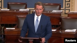 "FILE - U.S. Senator Jeff Flake, R-Ariz., speaks on the Senate floor in Washington, Oct. 24, 2017. He says he's had a ""long-term interest"" in Zimbabwe and thinks President Robert Mugabe will go down in history ""as a long-serving thug."""