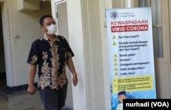 Seorang staf UGM melintas di depan poster terkait Virus Corona di kampus tersebut. (Foto:VOA/ Nurhadi)