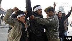 Поліцейський зупиняє демонстранта в Кашмірі