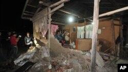 Warga setempat dan wartawan memeriksa sebuah rumah yang hancur akibat gempa 6,3 skala Richter di Sigi, Sulawesi Tengah (19/3).