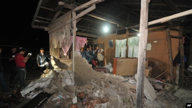 Warga setempat dan wartawan memeriksa sebuah rumah yang hancur akibat gempa 6,3 skala Richter di Sigi, Sulawesi. (Foto: Dok)