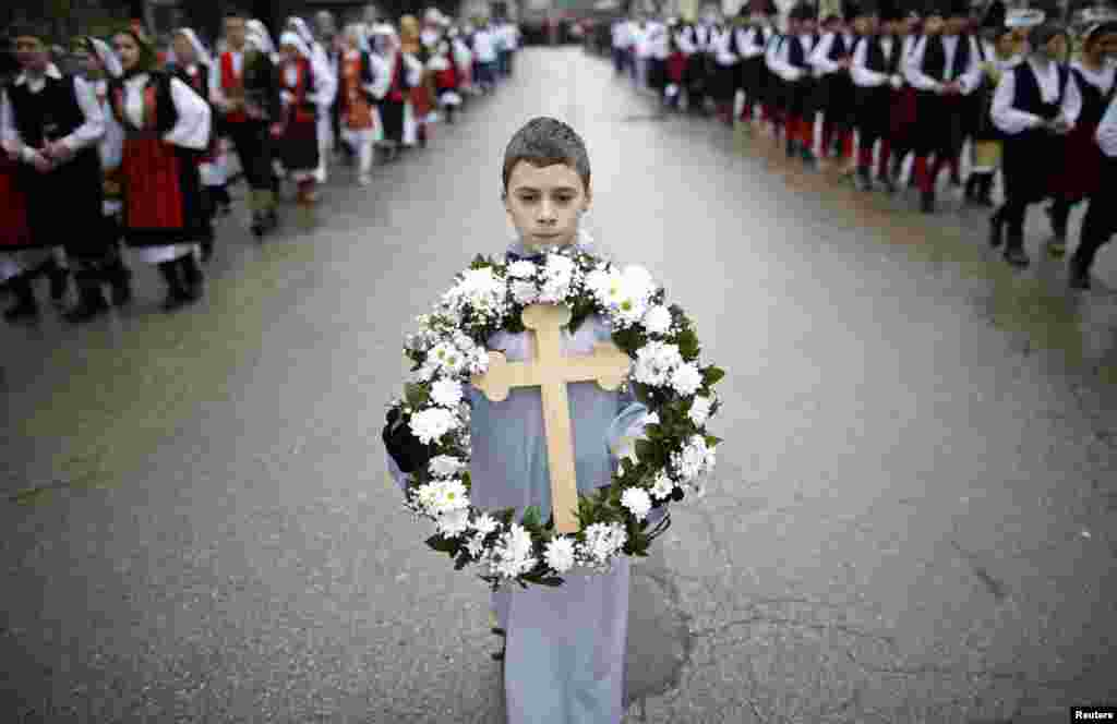 A boy carries a cross during Epiphany Day celebrations in Prijedor, Bosnia and Herzegovina. Orthodox priests throughout the country bless the waters by throwing a cross into it as worshippers try to retrieve it, with a strong belief that catching the cross brings health and prosperity to the person who catches it.
