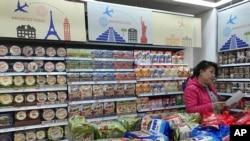 Seorang pedagang sedang menyusun stok bahan makanan impor di sebuah mall di Beijing, China, 17 Maret 2017.
