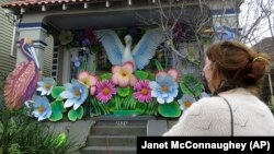 Caroline Thomas is a designer looking at a house decorated like a parade float in New Orleans for Mardi Gras, on Friday, Jan. 8, 2021. (AP Photo/Janet McConnaughey)