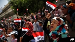 "Yemeni children chant slogans and wave Yemeni flags that read ""Yemen one"" in Arabic, during a protest in Sana'a against Saudi-led airstrikes in Yemen, June 6, 2015."