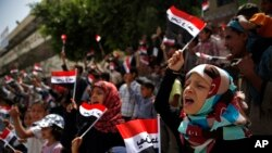 "Anak-anak Yaman meneriakkan slogan dan mengibarkan bender Yaman yang bertuliskan ""Satu Yaman"" dalam bahasa Arab, pada sebuah protes di Sana'a menentang serangan udara yang dipimpin oleh Arab Saudi di Yaman, 6 Juni 2015."