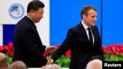 法國總統馬克龍在上海舉行的中國國際進口博覽會開幕式上講話後與中國國家主席習近平握手。(2019年11月5日)