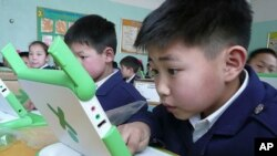 A boy in Mongolia checks out his computer after receiving it from 'One Laptop Per Child'.