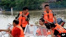 Regu penyelamat membantu warga menyebrangi jalanan yang terkena banjir di China Selatan (Foto: dok). Sembilan propinsi di wilayah China Selatan dikabarkan telah dihantam badai, banjir dan tanah longsor sejak Selasa (14/5)/