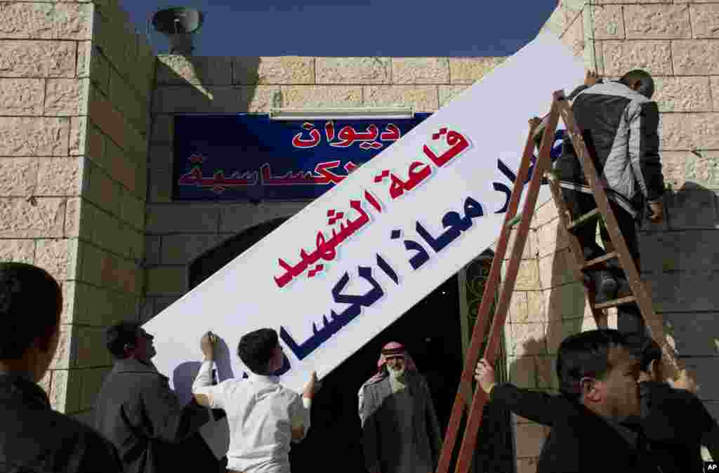 کارگران به نصب بنری بر سر در ورودی دیوان محل اجتماع قبيله الکساسبه، در نزدیکی کرک مشغولند. روی بنر به عربی نوشته شده است، «سالن خلبان شهید معاذالکساسبه» -- ۱۵ بهمن ۱۳۹۳ (۴ فوريه ۲۰۱۵)