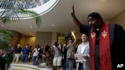 """FILE - Rev. William Barber, president of the North Carolina chapter of the NAACP, speaks to protesters and demonstrators outside the House and Senate chambers at the state legislature during the NAACP-led """"Moral Monday"""" protests at the General Assembly in Raleigh, North Carolina, July 1, 2013."""