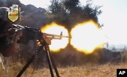 FILE - In this file image taken from video obtained from the Shaam News Network, a jihadi-led rebel fighter fires a gun in a valley in Latakia province, Syria. Rebels killed at least 190 civilians and abducted more than 200 during an offensive against pro-regime villages, committing a war crime, an international human rights group said, Oct. 11, 2013.