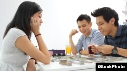 A group of friends play a board game at a cafe.