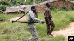 Des soldats alliés au président Alassane Ouattara traversent un terrain de camping à distance désert le long de la piste forestière menant de Bloléquin, vers la frontière entre la Côte d'Ivoire de l'ouest avec le Libéria, 1er juin 2011.