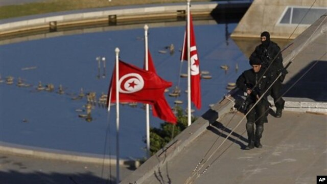 Soldiers stand guard atop a building the center of Tunis, 15 Jan 2011