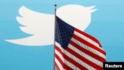 FILE - The Twitter Inc. logo is shown with the U.S. flag during the company's IPO on the floor of the New York Stock Exchange in New York, Nov. 7, 2013.