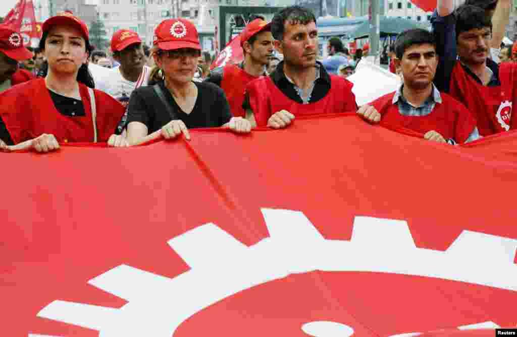 Para anggota serikat dagang meneriakkan slogan-slogan anti Perdana Menteri Recep Tayyip Erdogan saat berpawai di Alun-Alun Taksim di Istanbul (5/6). (Reuters/Yannis Behrakis)