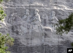 FILE - This June 23, 2015, file photo shows a carving depicting confederates Stonewall Jackson, Robert E. Lee and Jefferson Davis, in Stone Mountain, Ga.