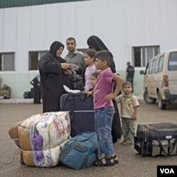 Keluarga Palestina menunggu untuk menyeberang ke Mesir melalui tempat penyeberangan di Rafah (28/5).