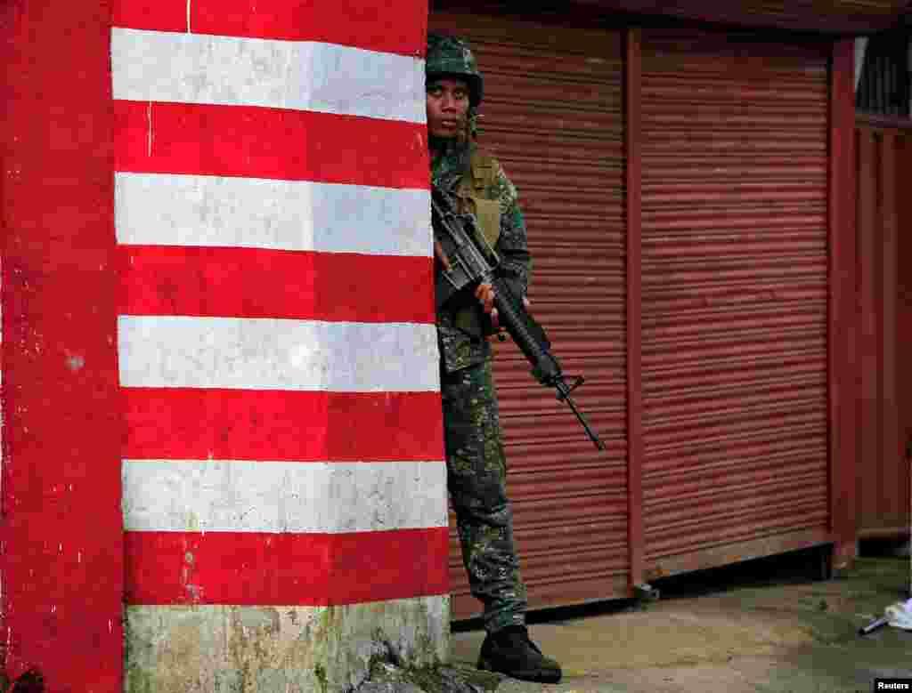 Seorang tentara Filipina mengambil posisi dalam pertempuran melawan militan kelompok Maute yang berafiliasi dengan ISIS di Marawi, Filipina selatan.