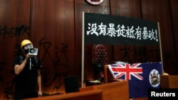 一名进入香港立法会的抗议者站在挂在立法会内的香港殖民地旗帜旁使用扩音喇叭讲话。(2019年7月1日)